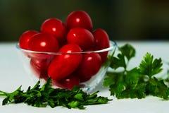Tomates et persil dans une tasse sur la table Images stock
