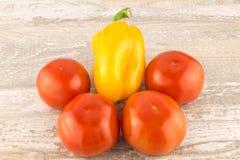 Tomates et poivrons doux de jaune sur une fin en bois blanche de fond  photos stock