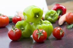 Tomates et poivrons verts rouges sur une table sur le fond des légumes Tomates et poivrons frais sur une table brune en bois Photos stock