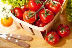 Tomates et salade dans le panier sur la table en bois Photo stock