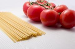 Tomates et spaguetti sur cru Photo stock