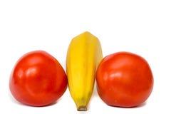 Tomates exóticos y plátano rojos y deliciosos con el fondo blanco Imágenes de archivo libres de regalías