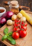 Tomates fraîches avec des légumes et basilic sur le conseil en bois Image libre de droits