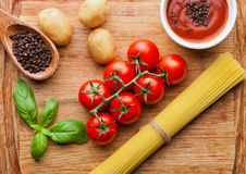 Tomates fraîches avec des légumes et spagetti sur le conseil en bois Images stock