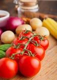Tomates fraîches avec des légumes sur le conseil en bois Photo stock