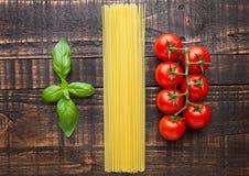 Tomates fraîches avec le spagetti et le basilic crus sur le fond de substance collante Photographie stock libre de droits
