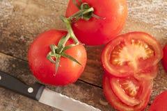 Tomates fraîches coupées en tranches et entières sur la vigne Photo libre de droits