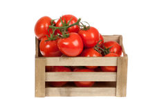 Tomates fraîches dans un isolat de caisse en bois sur un blanc Photographie stock