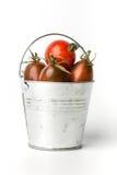 Tomates fraîches dans un seau sur le fond blanc Photo libre de droits