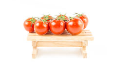 Tomates fraîches de nature avec la vigne verte sur en bois Photographie stock libre de droits