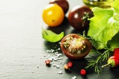 Tomates fraîches de raisin avec les feuilles et le sel de salade Photo libre de droits