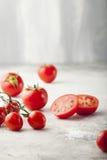 Tomates fraîches de raisin, sel de mer avec une tomate divisée en deux Photographie stock libre de droits