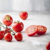 Tomates fraîches de raisin, sel de mer avec une tomate divisée en deux Images libres de droits
