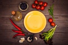 Tomates fraîches, poivre de piment et d'autres épices et herbes autour de plat jaune moderne au centre de la table en bois Vue su Photographie stock