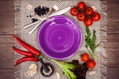 Tomates fraîches, poivre de piment et d'autres épices et herbes autour de plat pourpre moderne au centre de la serviette en bois  Photo stock