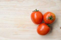 Tomates fraîches rouges sur le fond en bois de table Images stock