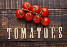 Tomates fraîches sur le conseil en bois avec des lettres ci-dessous Images stock