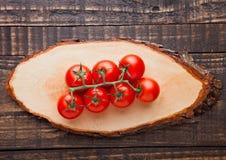 Tomates fraîches sur le fond de conseil en bois et de grunge Image libre de droits