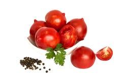Tomates fraîches sur le fond vert de colza Photographie stock libre de droits