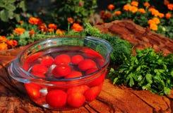 Tomates fraîches tombant dans l'eau pure Image stock