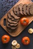 Tomates frescos con el pan hecho en casa, mintiendo en el tablero de madera Foto de archivo