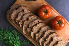 Tomates frescos con pan hecho en casa y verdes, mentira en el tablero de madera Foto de archivo