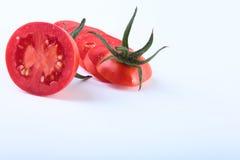 Tomates frescos cortados com as folhas verdes no fundo branco Fotos de Stock