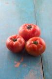 Tomates frescos crudos en tabla de cortar azul Fotos de archivo