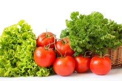 Tomates frescos e ervas diferentes em uma cesta de vime Foto de Stock Royalty Free