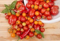 Tomates frescos e outros vegetais que derramam na placa de corte Fotografia de Stock