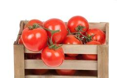 Tomates frescos em um isolado da caixa de madeira em um branco Foto de Stock