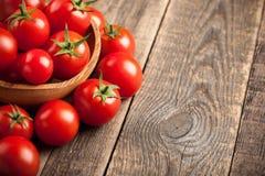 Tomates frescos em uma bacia de madeira na tabela de madeira Imagens de Stock Royalty Free