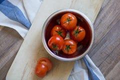 Tomates frescos em uma placa de desbastamento Imagem de Stock