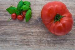 Tomates frescos en una tabla de madera Imagen de archivo