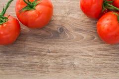 Tomates frescos en una tabla de madera Imágenes de archivo libres de regalías