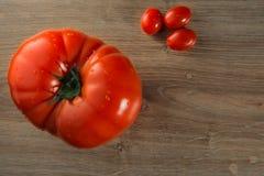 Tomates frescos en una tabla de madera Foto de archivo libre de regalías