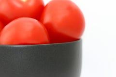 Tomates frescos encantadores en un tazón de fuente negro Imágenes de archivo libres de regalías