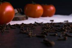 Tomates frescos, pan hecho en casa y clavos Foto de archivo