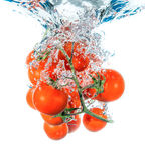 Tomates frescos que caen en agua Imágenes de archivo libres de regalías