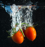 Tomates frescos que caen en agua Foto de archivo libre de regalías