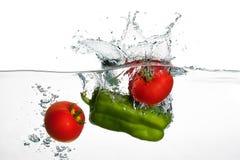Tomates frescos y chapoteo de la pimienta verde en el agua aislada en pizca Imágenes de archivo libres de regalías