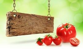 Tomates frescos y tablero de madera Foto de archivo libre de regalías