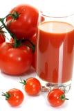 Tomates frescos y un vidrio lleno de jugo de tomate. Fotos de archivo libres de regalías