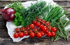 Tomates frescos y verduras verdes Cebolla, eneldo, Rosemary, perejil, cebolletas y tomillo en la tabla de madera vieja Imagenes de archivo