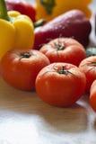 Tomates grandes y brillantes en la tabla de cocina Foto de archivo libre de regalías