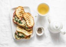 Tomates grelhados quentes, espinafres, sanduíches da mussarela e chá verde - café da manhã saudável, petisco em um fundo claro fotografia de stock