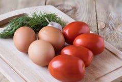 Tomates, huevos, ajo y eneldo en una tabla de cortar Fotos de archivo libres de regalías