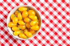 Tomates jaunes sur la nappe de pique-nique photos stock