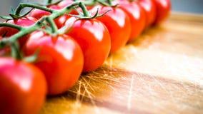 Tomates jugosos rojos en una tabla de cortar imagen de archivo