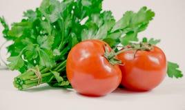 Tomates juteuses mûres et persil vert dans la cuisine Photo libre de droits